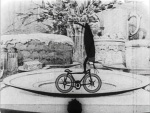 Still from 'Bug Vaudeville' featuring a cockroach stunting on a bicycle